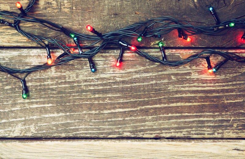 Luzes de Natal coloridas no fundo rústico de madeira Imagem filtrada foto de stock