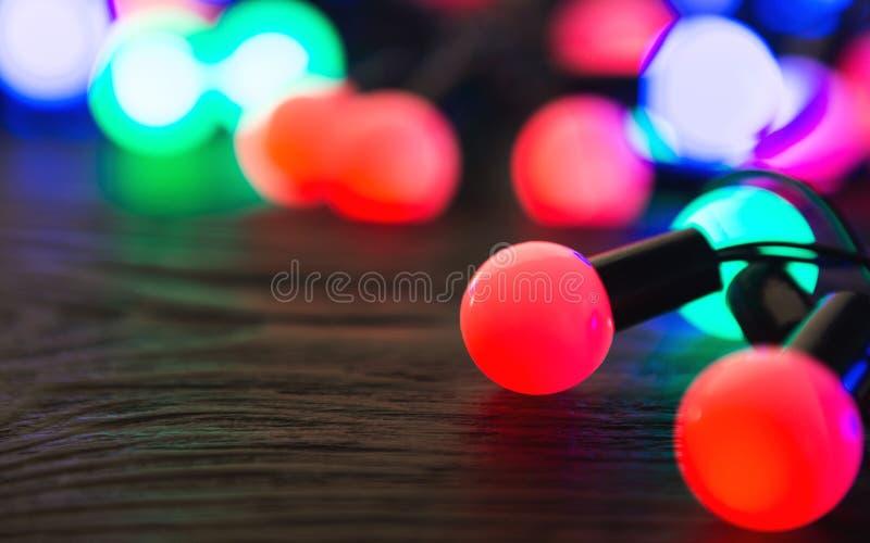 Luzes de Natal coloridas que incandescem no fundo escuro foto de stock