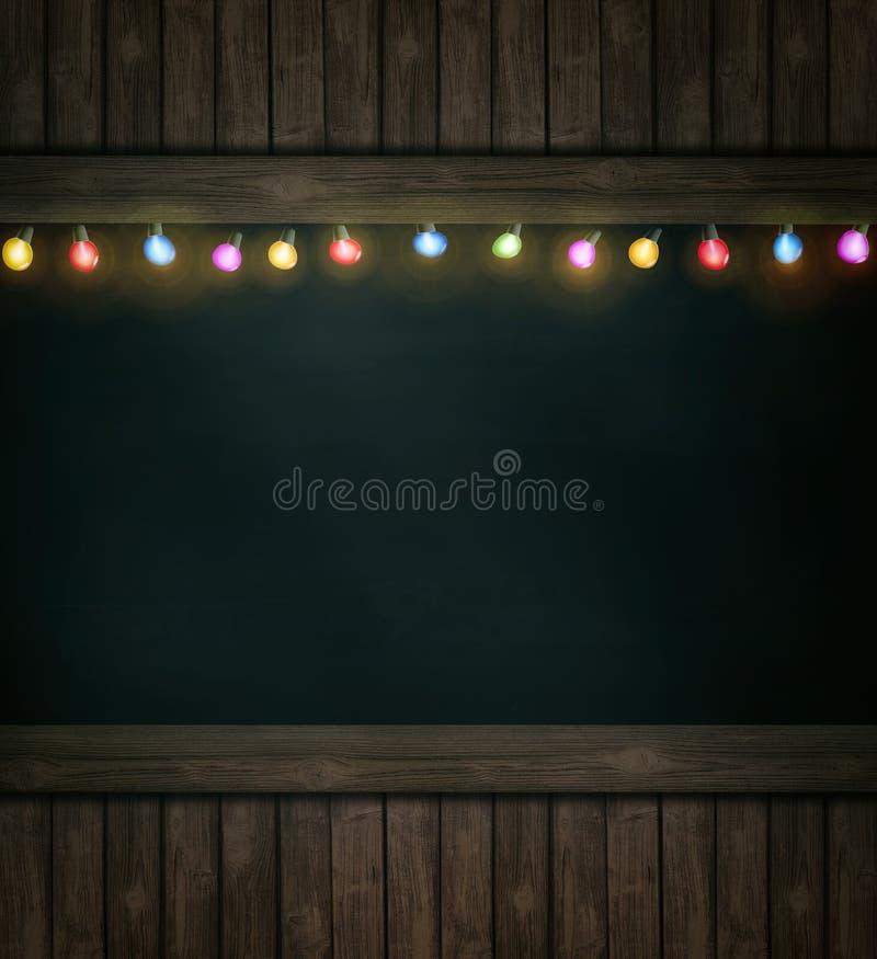 Luzes de Natal no quadro-negro de madeira fotografia de stock royalty free