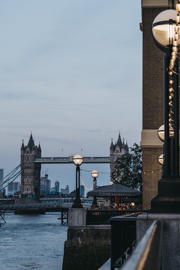 Luzes de rua iluminadas ao longo do rio Tamisa, ponte no fundo, foco seletivo da torre imagem de stock royalty free