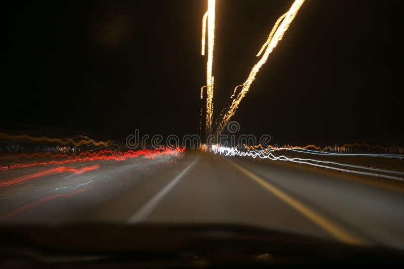 Luzes de rua no carro de pressa na noite, movimento claro com opinião do obturador da velocidade lenta do interior da parte diant fotos de stock