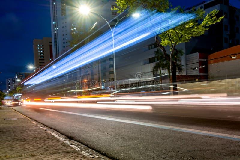Luzes de um ônibus que passa perto em uma pintura longa da luz da exposição nas ruas imagens de stock