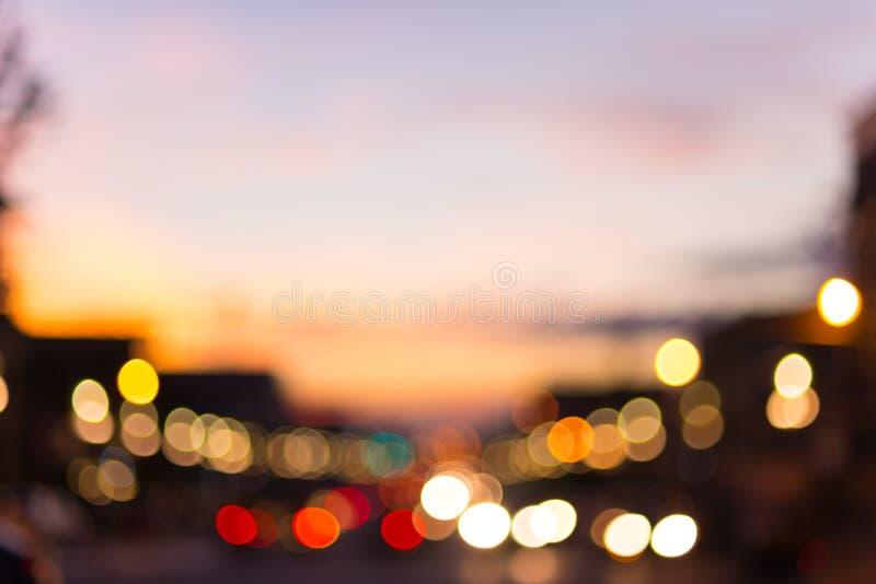 Luzes Defocused do tráfego e da cidade na rua grande urbana no crepúsculo foto de stock
