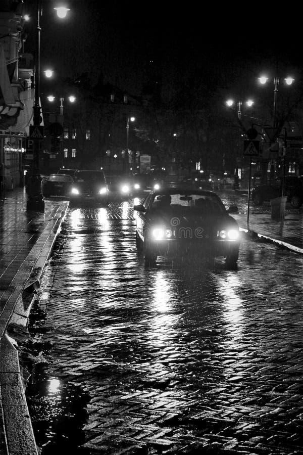 Luzes do carro em uma noite chuvosa imagem de stock