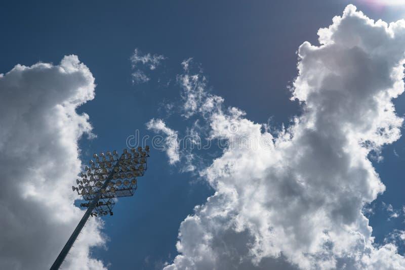 Luzes do estádio dos esportes contra um céu parcialmente nebuloso imagens de stock