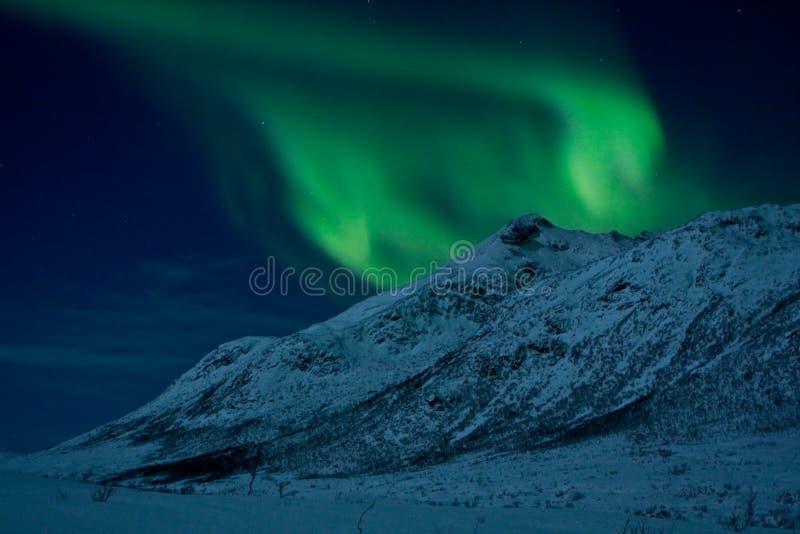 Luzes do norte atrás de uma montanha foto de stock