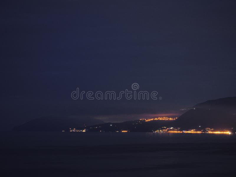Luzes do sity da noite a custo do mar fotografia de stock