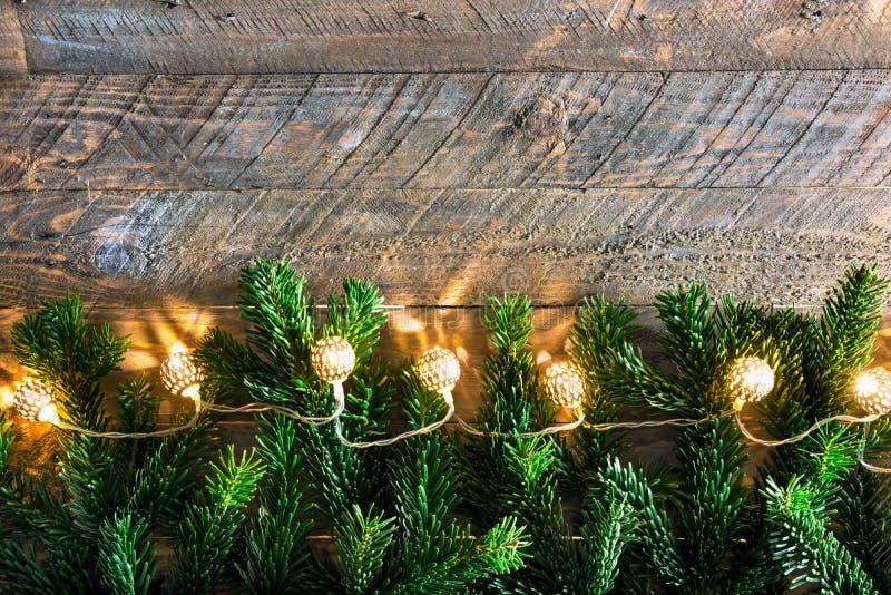 Luzes efervescentes douradas da festão dos ramos de árvore do abeto do cartaz do cartão dos anos novos do Natal no feriado de mad imagens de stock