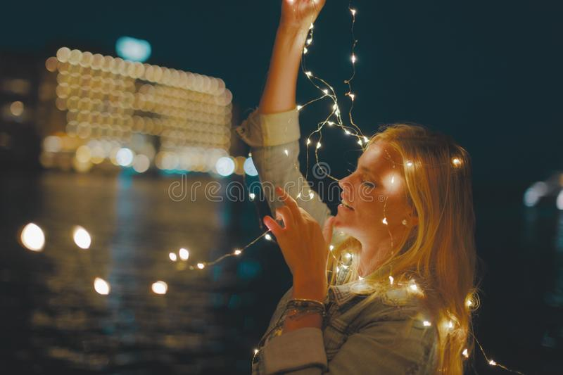 Luzes feericamente da festão loura nova sensual da mulher na noite fotografia de stock