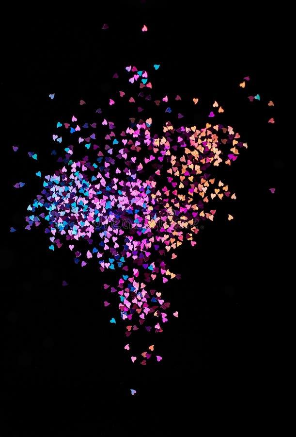 Luzes multicoloridos do bokeh, corações minúsculos em um fundo preto, vista superior, carnaval, convite do partido da noite ou fe fotografia de stock