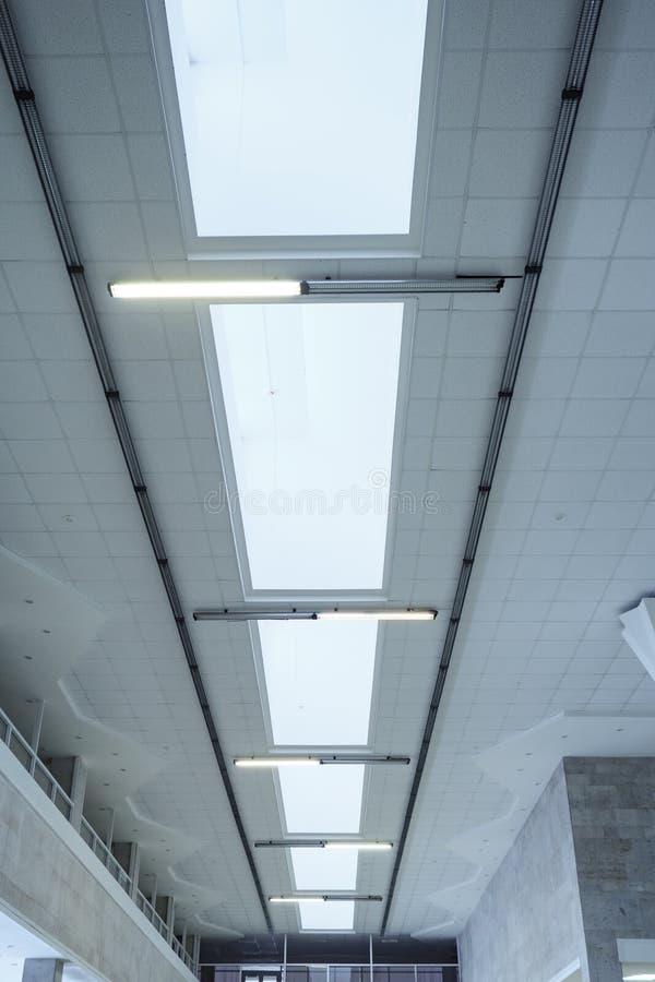 Luzes na linha longa no teto da construção industrial do escritório imagem de stock