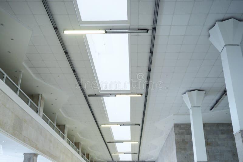 Luzes na linha longa no teto da construção industrial do escritório, salão de exposição foto de stock