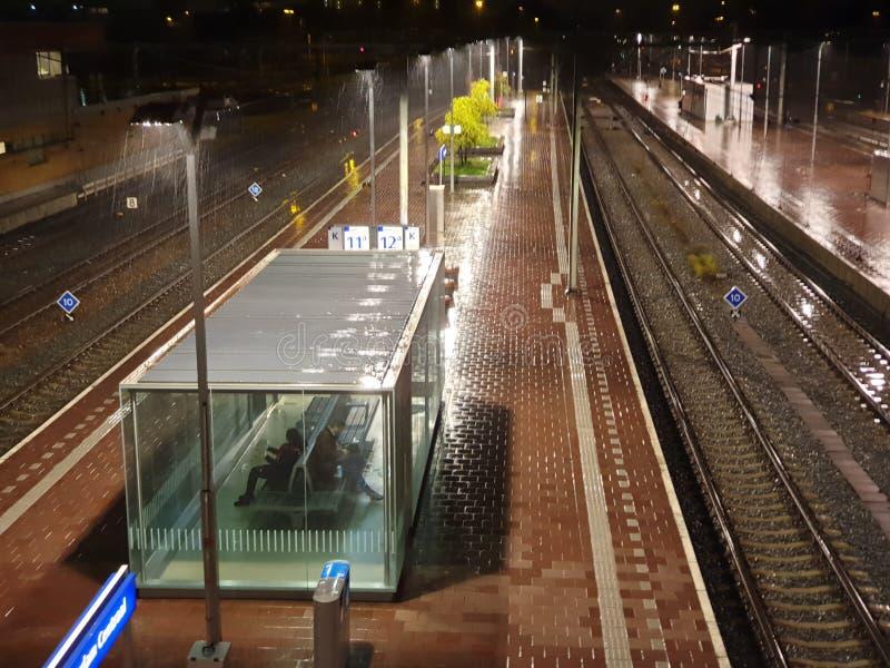 Luzes nas plataformas da estação de comboios Roterdão Central à chuva fotos de stock royalty free