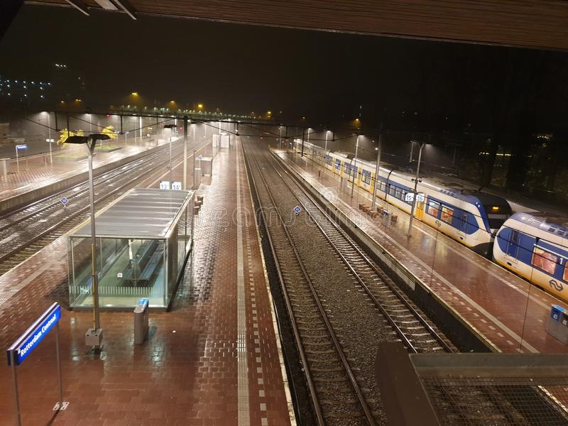 Luzes nas plataformas da estação de comboios Roterdão Central à chuva foto de stock