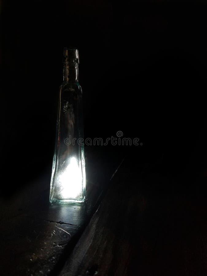 Luzes que eminating convenientemente de uma garrafa antiga imagens de stock