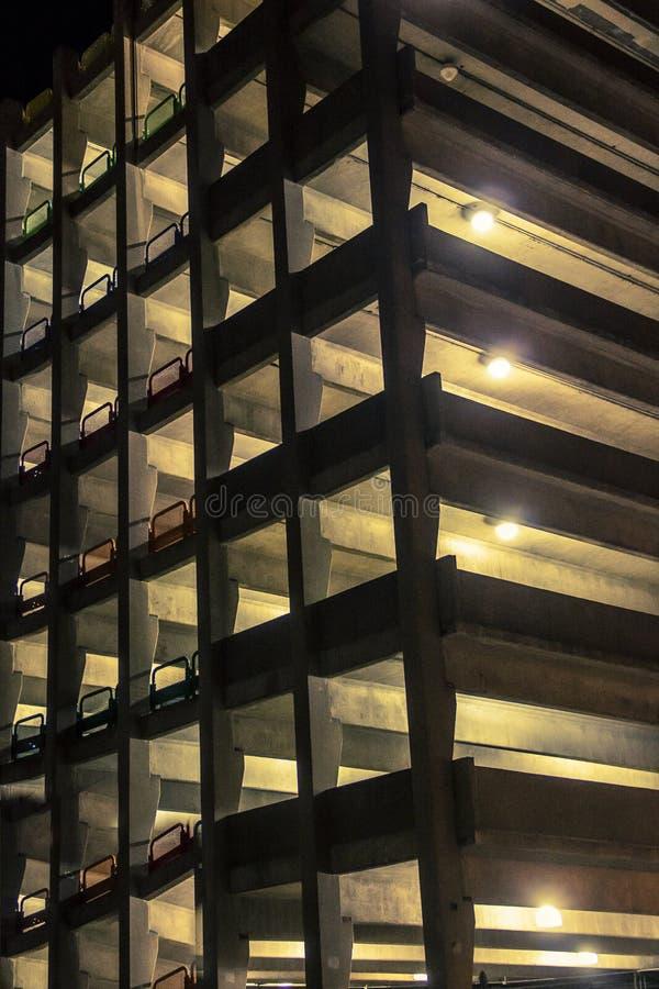 Luzes que incandescem de uma garagem de estacionamento na noite foto de stock