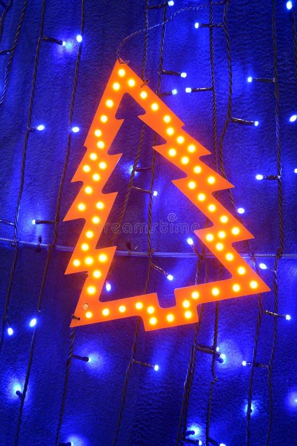 Luzes retros sob a forma da árvore de Natal entre luzes de Natal foto de stock