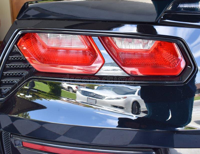 Luzes vermelhas brilhantes da cauda de um exterior do carro de esportes que reflete tudo ao redor fotografia de stock royalty free