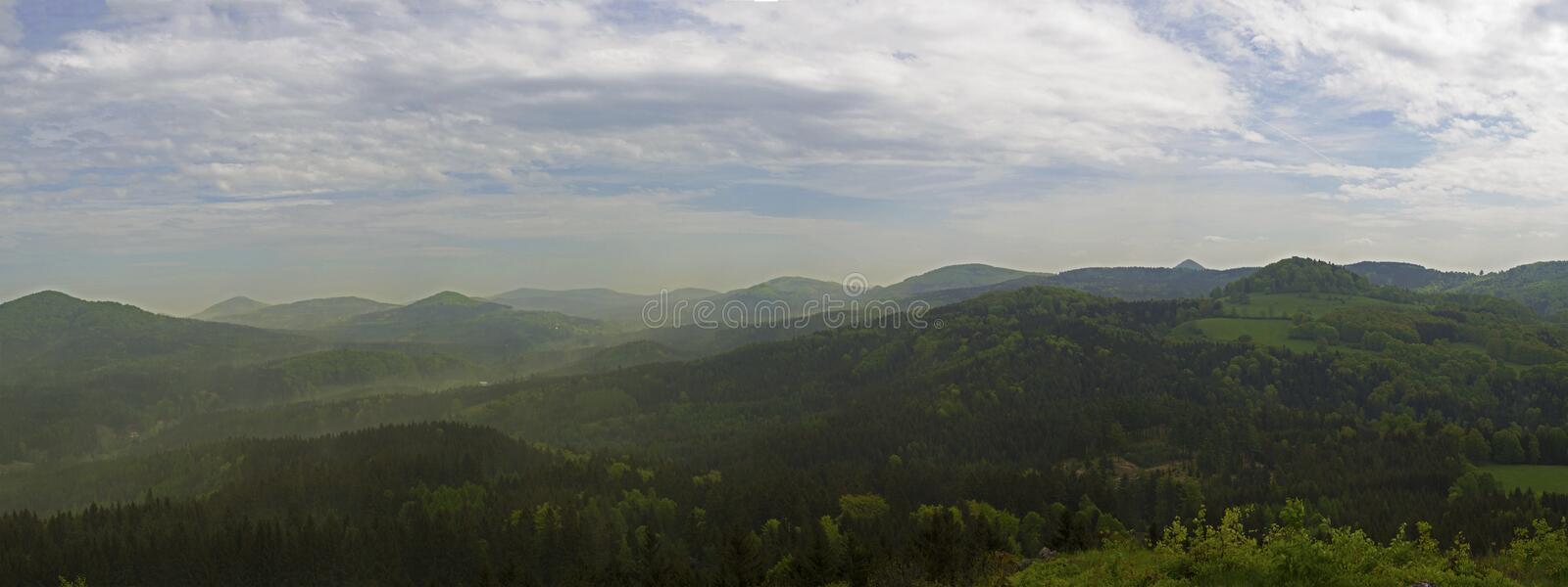 Luzicke hory mountains wide panorama, skyline view from hill stredni vrch, green forest and blue sky, white clouds background stock photography