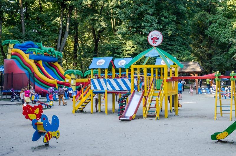 Lviv, de Oekraïne - 19 Augustus 2015: De speelplaats van kinderen met schommeling en opblaasbare trampoline in pretpark waar de k royalty-vrije stock foto