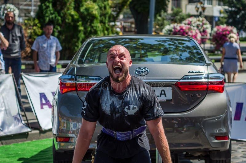LVIV, DE OEKRAÏNE - AUGUSTUS 2017: De sterke atleet de bodybuilder heft de Toyota-auto voor enthousiaste toeschouwers bij Sterk o stock fotografie