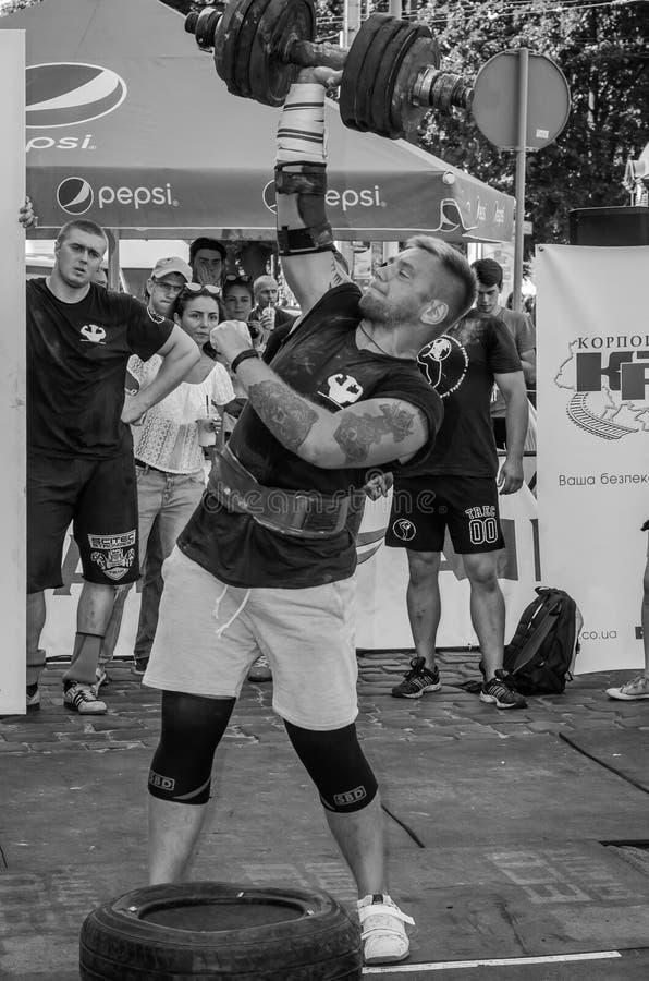 LVIV, DE OEKRAÏNE - AUGUSTUS 2015: De sterke atletenatleet heft zwaargewicht op Strongmen-spelen op stock afbeeldingen