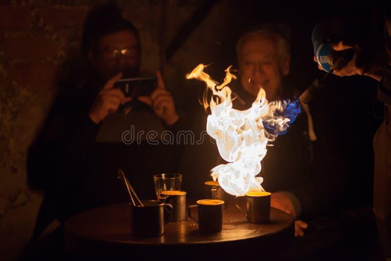 LVIV, de OEKRAÏNE - December 2, 2018 De toeristen letten op de voorbereiding van extreme koffie Gekarameliseerde koffie De brand  royalty-vrije stock foto