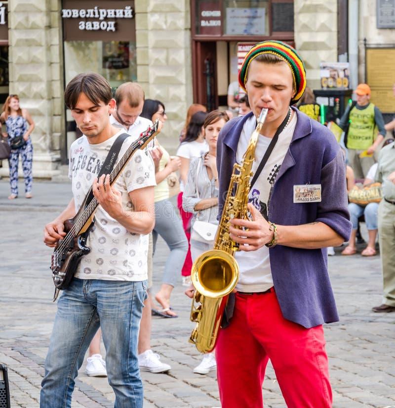 Lviv, de Oekraïne - Juli 2015: Musici die de saxofoon en de gitaar spelen die een overleg in het Marktvierkant geven in Lviv vóór royalty-vrije stock fotografie
