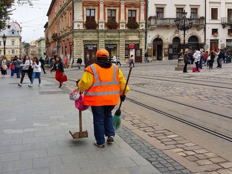 Lviv, de Oekraïne - 7 oct 2018: Een werknemer van de communale economie in de centrale vierkante Markt van de oude stad Oude Arch royalty-vrije stock foto's
