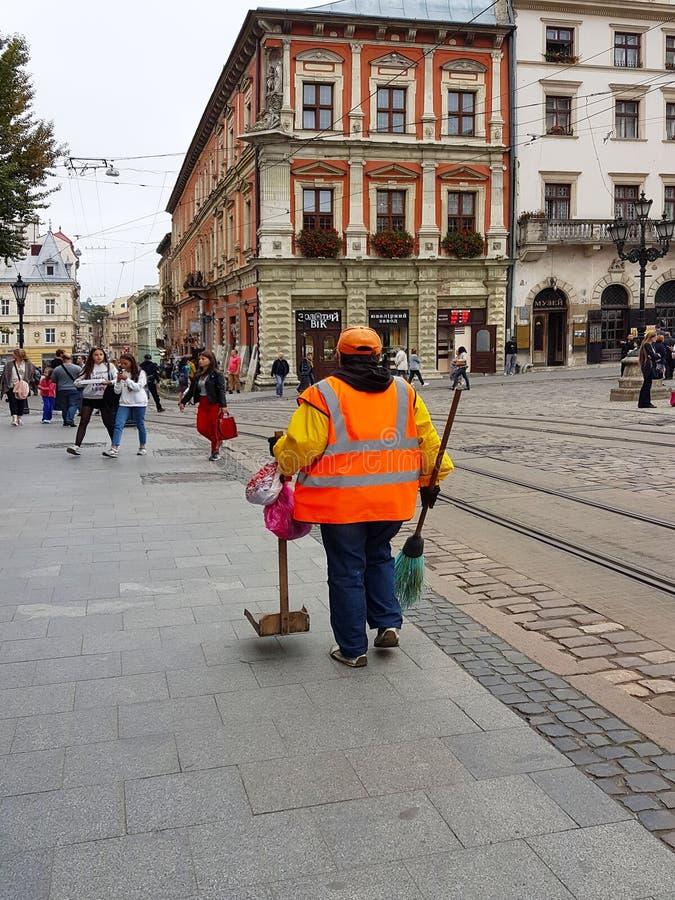 Lviv, de Oekraïne - 7 oct 2018: Een werknemer van de communale economie in de centrale vierkante Markt van de oude stad Oude Arch royalty-vrije stock fotografie