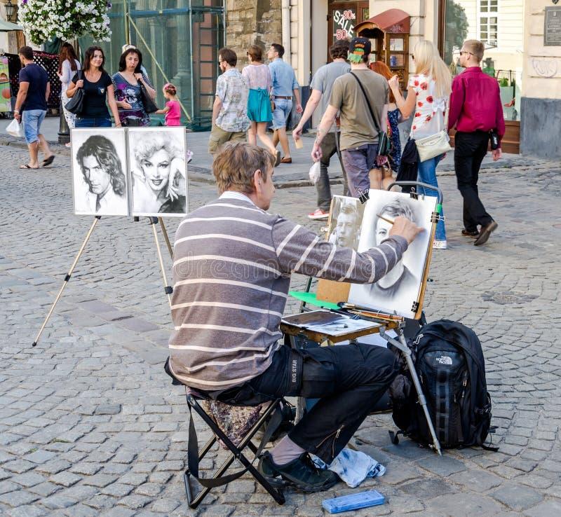 Lviv, Ucrânia - em julho de 2015: O artista masculino da rua tira um retrato de um homem com uma escova na lona em Lviv, no merca fotos de stock