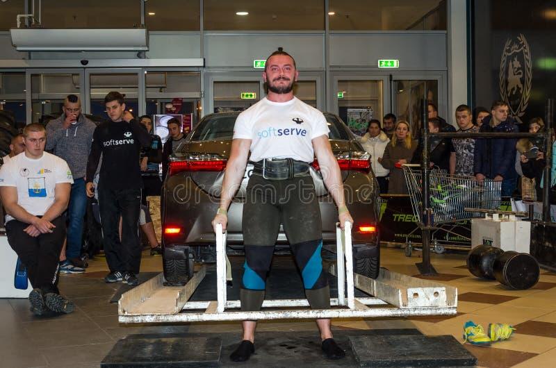 LVIV, UCRÂNIA - EM NOVEMBRO DE 2016: O homem forte forte do atleta levanta um carro pesado Toyota Corolla imagens de stock