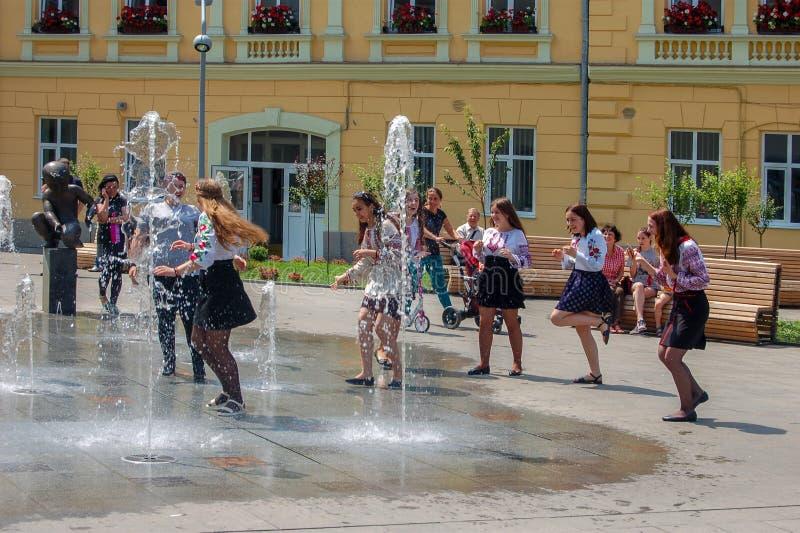 Lviv, Ucrânia, o 27 de junho de 2017 Moças na roupa nacional nas fontes abertas na rua do verão imagem de stock royalty free