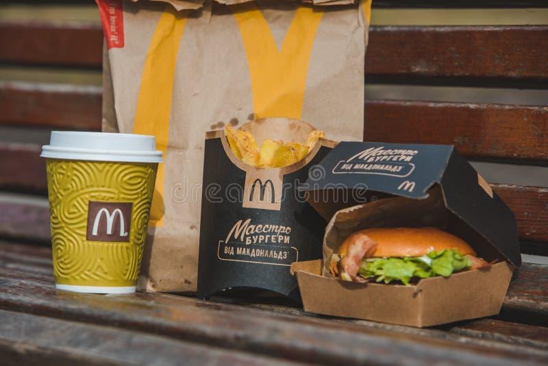 LVIV, UCR?NIA - 28 de fevereiro de 2019: hamburguer na caixa com o copo de caf? das batatas da fritada Fast food fotos de stock
