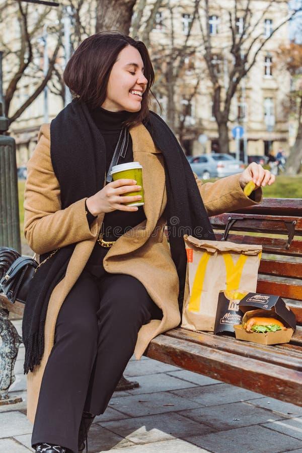 LVIV, UCR?NIA - 28 de fevereiro de 2019: mulher que come o fast food no banco da cidade imagem de stock royalty free