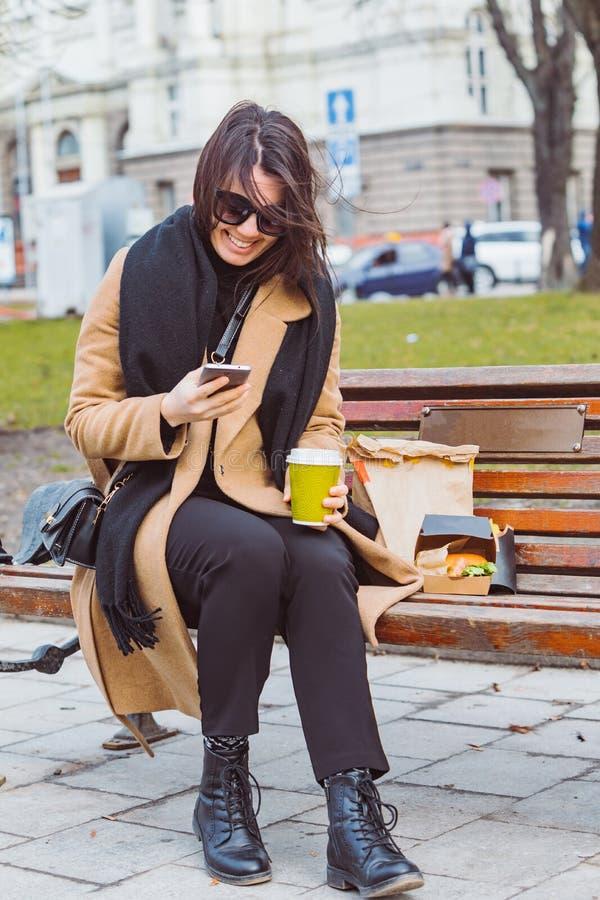 LVIV, UCR?NIA - 28 de fevereiro de 2019: mulher que come o fast food no banco da cidade fotos de stock royalty free