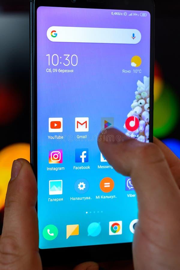 LVIV, UCRÂNIA - 9 DE MARÇO DE 2019: O homem guarda o smartphone em suas mãos close-up e abre a aplicação a Google Play sobre fotografia de stock royalty free