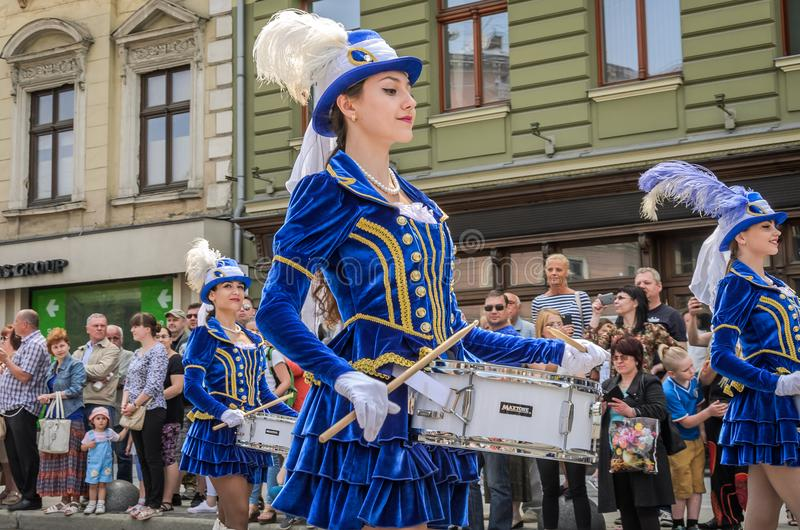 LVIV, UCRÂNIA - EM MAIO DE 2018: Moças bonitos com os cilindros em trajes e em chapéus azuis do carnaval com as penas durante a p fotos de stock