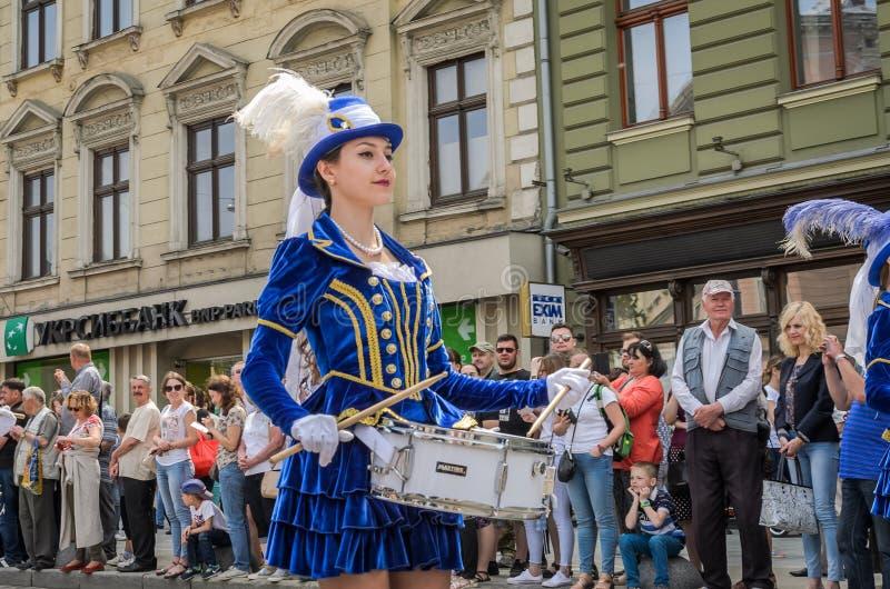 LVIV, UCRÂNIA - EM MAIO DE 2018: Moças bonitos com os cilindros em trajes e em chapéus azuis do carnaval com as penas durante a p imagem de stock royalty free
