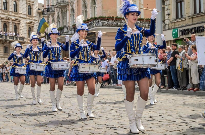 LVIV, UCRÂNIA - EM MAIO DE 2018: Moças bonitos com os cilindros em trajes e em chapéus azuis do carnaval com as penas durante a p foto de stock