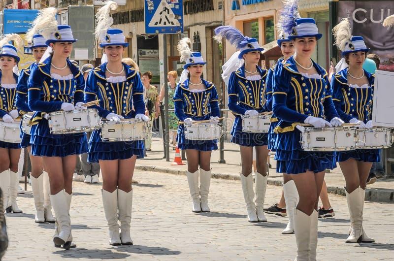 LVIV, UCRÂNIA - EM MAIO DE 2018: Moças bonitos com os cilindros em trajes e em chapéus azuis do carnaval com as penas durante a p fotografia de stock