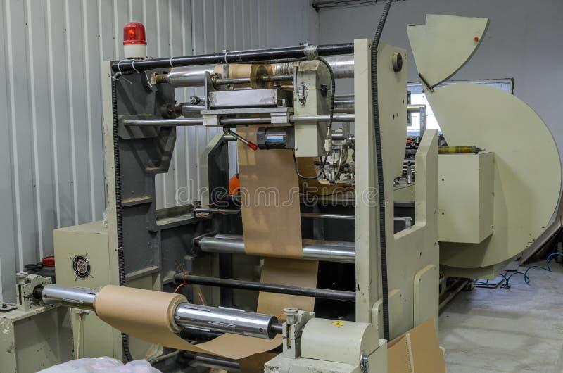 LVIV, UCRÂNIA - EM NOVEMBRO DE 2018: Grande saco de papel que faz a máquina na fábrica imagem de stock