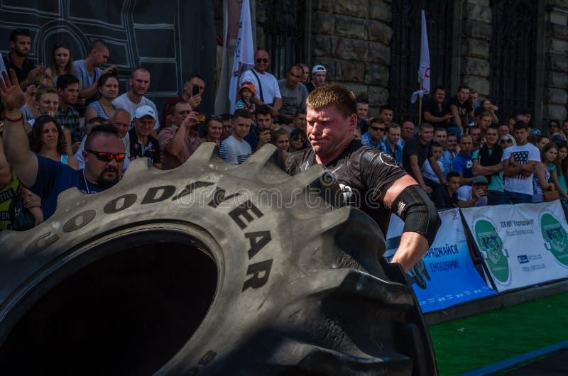 LVIV, UCRANIA - AGOSTO DE 2017: Un atleta fuerte estupendo aumenta una buena rueda enorme del año en las competencias delante del imágenes de archivo libres de regalías