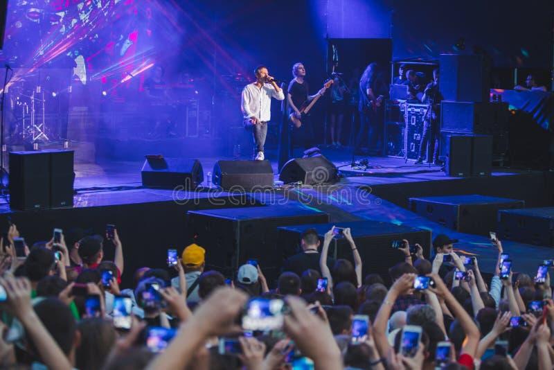 LVIV, UCRANIA - 18 de junio de 2019: cantante de la banda de rock en etapa con la muchedumbre del micrófono alrededor del tiroteo imagen de archivo