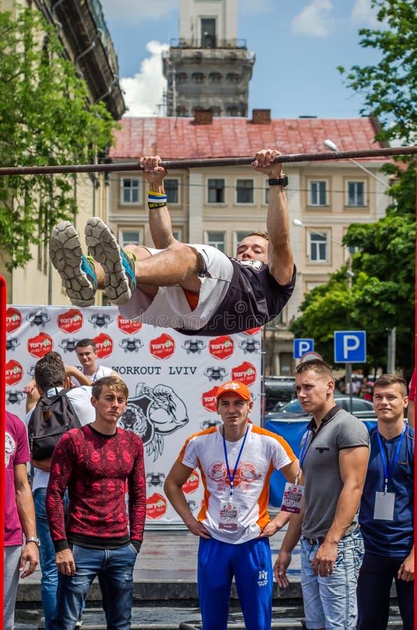LVIV, UCRANIA - JUNIO DE 2016: El atleta joven del muchacho demuestra su capacidad realizando diversos ejercicios y figuras en el fotografía de archivo libre de regalías