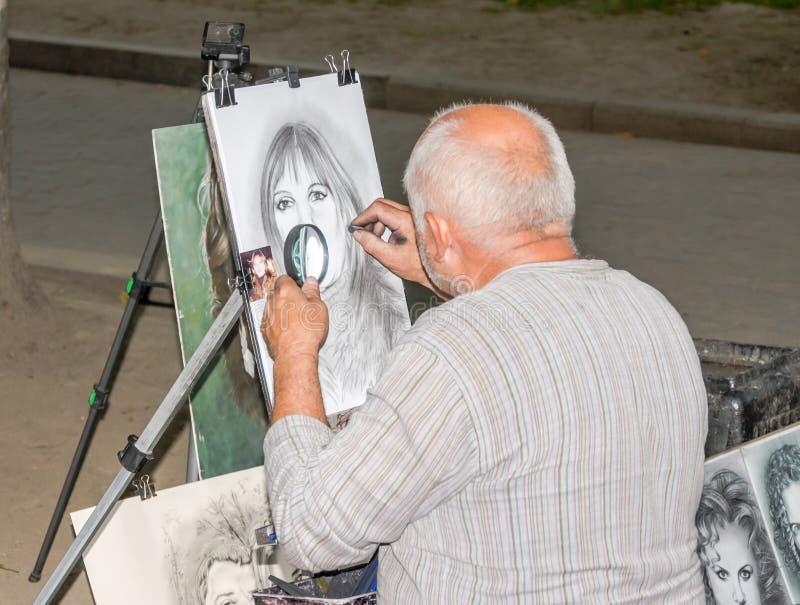 Lviv, Ucrania - junio de 2015: El pintor pinta un retrato de la muchacha de calle con el lápiz y el papel para las fotos fotos de archivo