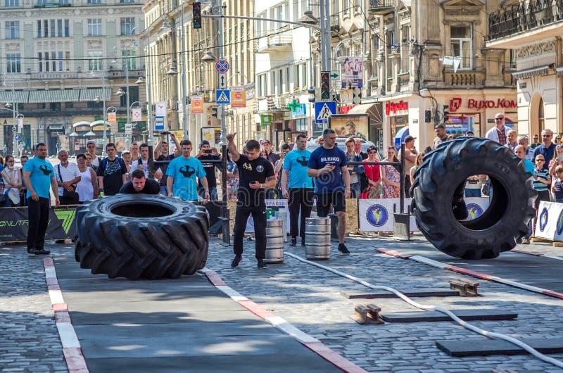 LVIV, UCRANIA - JUNIO DE 2016: Un hombre fuerte en el culturista de la forma de los deportes aumenta la rueda pesada en la calle foto de archivo libre de regalías