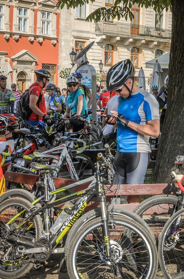 LVIV, UCRANIA - MAYO DE 2018: Un ciclista en forma de la bicicleta hace que el selfie en el teléfono en un motorista va de fiesta fotos de archivo libres de regalías