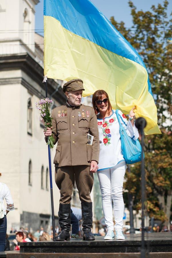 Lviv UKRAINA - Augusti 24, 2017: En veteran av den ukrainska rebelliska armén rymmer en flagga av Ukraina royaltyfria foton