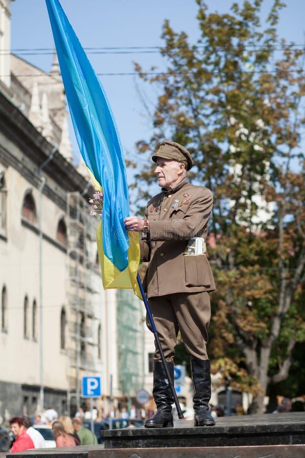 Lviv UKRAINA - Augusti 24, 2017: En veteran av den ukrainska rebelliska armén rymmer en flagga av Ukraina arkivbilder